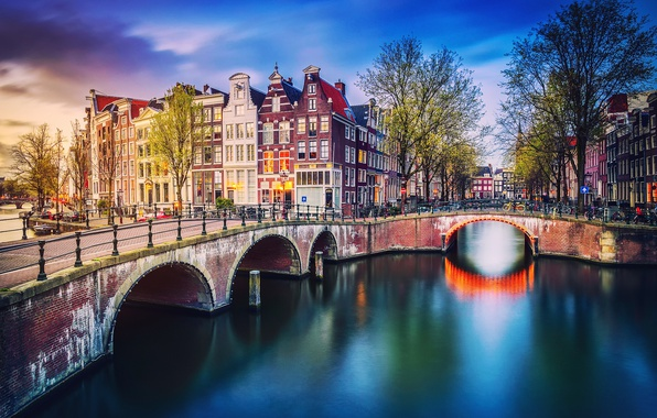 Картинка деревья, город, огни, дома, весна, вечер, Амстердам, канал, Нидерланды, мостик, велосипеды