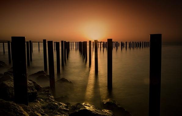 Картинка море, закат, берег, столбы