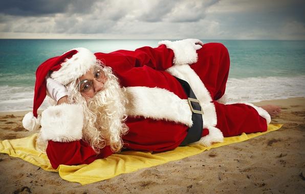 Картинка песок, море, солнце, облака, праздник, шапка, новый год, горизонт, очки, лежит, перчатки, шуба, борода, Санта …