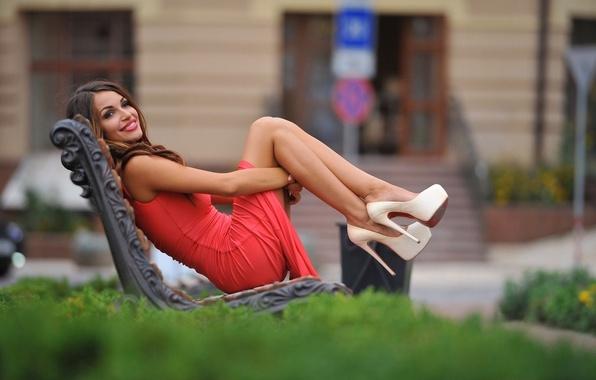 Картинка зелень, девушка, скамейка, улыбка, настроение, фигура, платье, брюнетка, прическа, туфли, ножки, в красном, боке