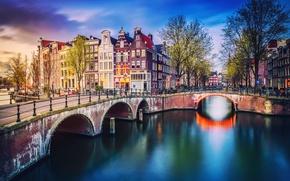 Картинка весна, вечер, Нидерланды, канал, Амстердам, огни, город, деревья, дома, велосипеды, мостик
