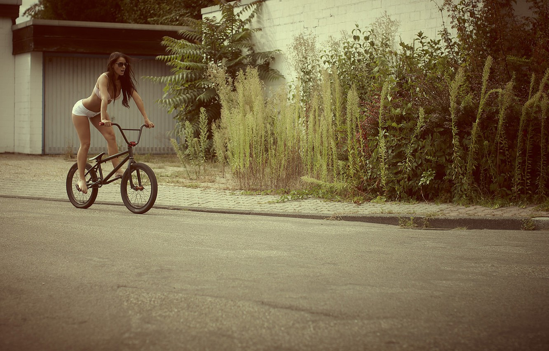 Фото обои дорога, девушка, велосипед, улица, шорты, нижнее белье, брюнетка, очки, sexy, кусты, kristina, melissa mendini