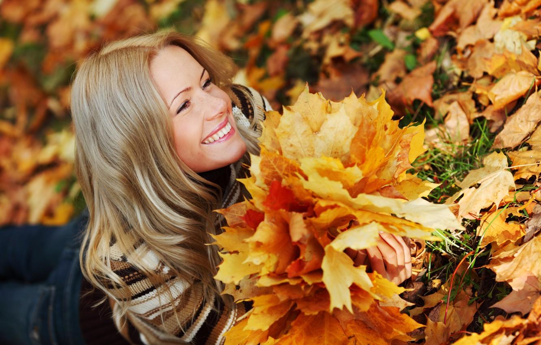 Фото обои осень, трава, взгляд, листья, девушка, улыбка, джинсы, блондинка, лежит, свитер
