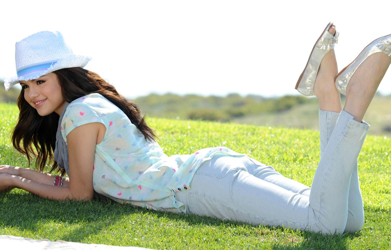 Фото обои зелень, солнце, улыбка, настроение, газон, шляпа, актриса, брюнетка, туфли, лежит, певица, на траве, Селена Гомес, …