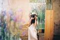 Картинка camera, bokeh, water, bottles, girl, hat, dress, house, wall, flowers, photo