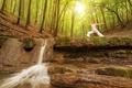 Картинка лес, солнце, в белом, девушка, гимнастика, майка, шатенка, деревья, брюки, водопад, природа, утро, поза