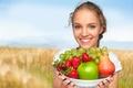 Картинка тарелка, ягоды, брюнетка, девушка, настроение, поле, солнце, виноград, клубника, природа, улыбка, боке, яблоко, фрукты, груша, ...
